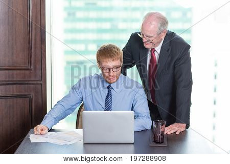 Closeup of smiling senior business man standing behind middle-aged colleague who is sitting at table and working on laptop computer with big window in background. Front view.