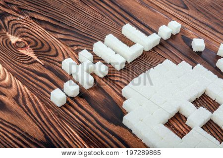 Close-up sugar cubes in a form of a terrible skull and cubes of sugar forming a word
