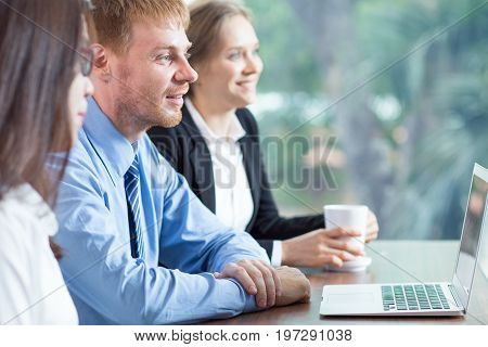 Closeup of three smiling adult business people sitting at table with laptop computer and attending presentation. Side view with big window and blurry green view outside in background.