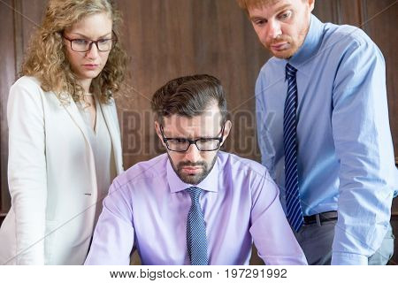 Closeup of three middle-aged business people thinking. One business man is sitting. Other male and female colleagues are standing behind.