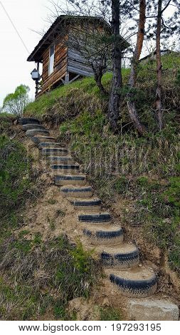 Stairs made of old tires and a wooden shed