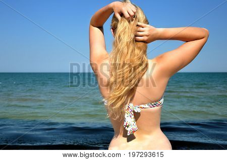Girl with black sunglasses and long hair looks at the sea