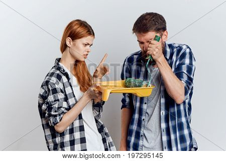 Young beautiful woman with a man with a beard on a light background holding stoic tools for repair.