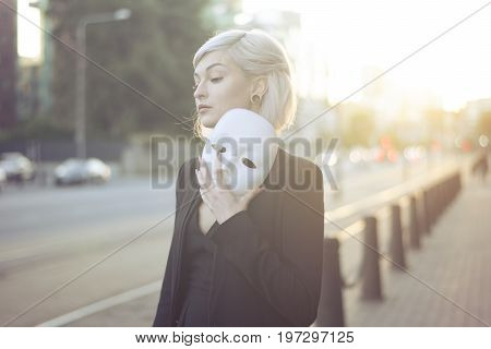 Young blond woman taking off a mask. Pretending to be someone else concept. outdoors on sunset