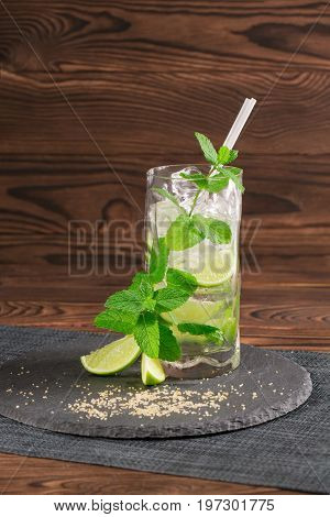 Close-up of a tasty colourful beverage with fresh slices of lime, straws, ice and mint twigs on a wooden background. Summer beverages. Alcoholic cocktails for summer parties. Copy space.