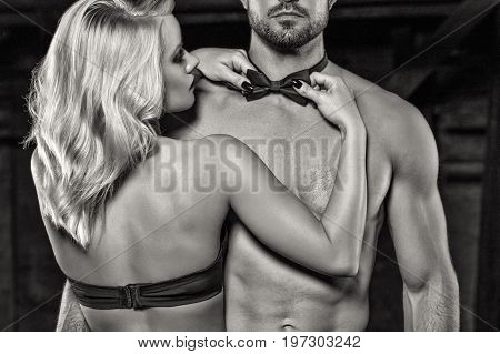 Sensual blonde woman straighten bow tie on naked sexy man strippers at bachelor party black and white