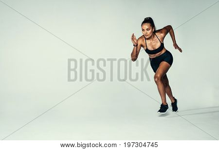 Full length shot of fitness woman running over grey background. Hispanic female runner working out in studio.