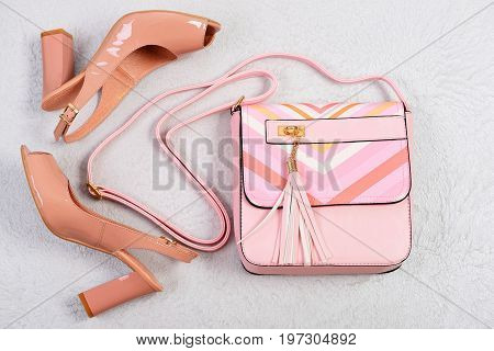 High Heel Sandals And Handbag On White Fabric Background