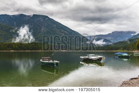 Boats at Sylvenstein lake on a gloomy autumn day. Germany