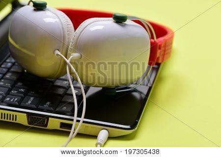 Headphones And Black Laptop. Electronics Isolated On Light Yellow Background.