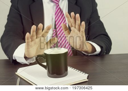 Stop coffee concept business man show hand and give up drinking