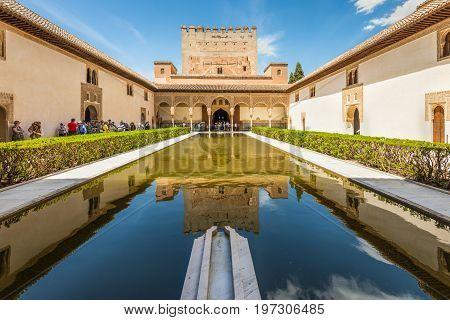 Granada Spain - May 19 2014: Tourists in the courtyard of the Myrtles (Patio de los Arrayanes) in La Alhambra Granada Spain.