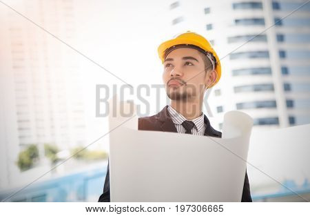 Young businessman with hard helmet holding yellow with blueprints in front of the site during the evening.