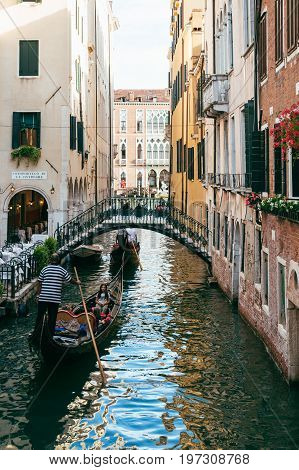 VENICE, ITALY - JULY 02, 2017: Gondolas on a narrow canal leading to Grand Canal in Venice. Gondola rides and tours are the city's iconic features and are very popular among tourists.