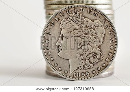 1896 Morgan Dollar coin stands against a stack of coins.