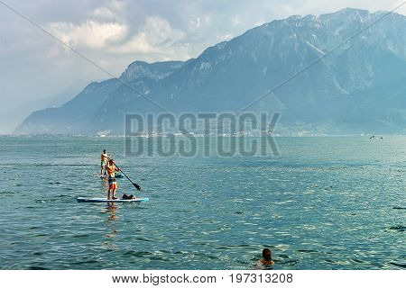 Vevey Switzerland - August 27 2016: People standing on Standup paddle surfing board on Geneva Lake in Vevey Vaud canton Switzerland