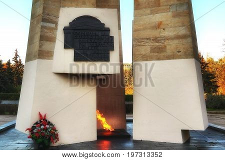 MOSCOW RUSSIA - OCTOBER 13 2015: Eternal flame and obelisk at MSU. Caption on black bas relief from russian: For students and teachers of Moscow state University fallen in battle for Soviet Motherland in great Patriotic war 1941-1945