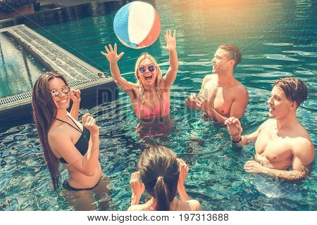 Group of friends in the swimming pool playing with ball