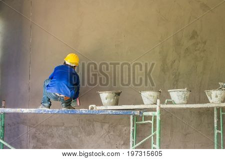 Construction workers plastering building wall using cement plaster mix of cement and sand at the construction site