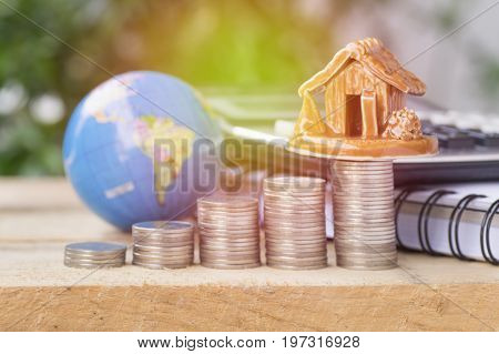 pile of coinsglobe and home concept in house finance on wood table