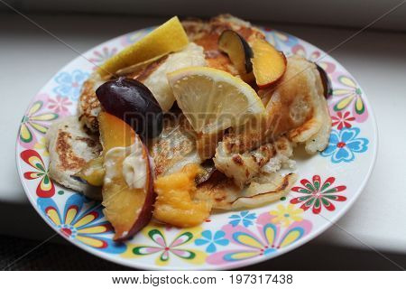 appetizing vegetarian sweet pancakes with ripe juicy summer fruits on the plate