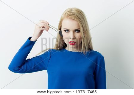 Girl applying makeup on face skin with powder brush. Pretty woman with blond long hair wearing blue dress isolated on white. Fashionable model. Fashion. Visage make up cosmetics and skincare
