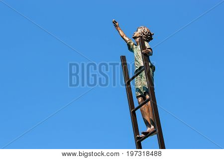 Montreux Switzerland - August 27 2016: Sculpture with a boy on the ladder at Geneva Lake embankment in Montreux Vaud canton Switzerland