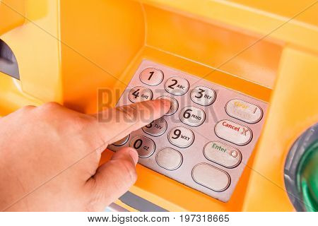 Close up of hand entering pin at an ATM. Finger about to press a pin code on a pad. Security code on an Automated Teller