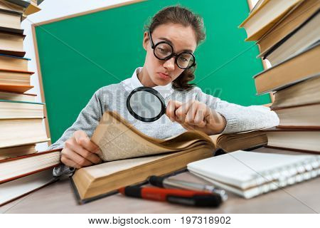Student with a magnifying glass seeks the answer in volume. Photo of girl keen on reading book. Education concept