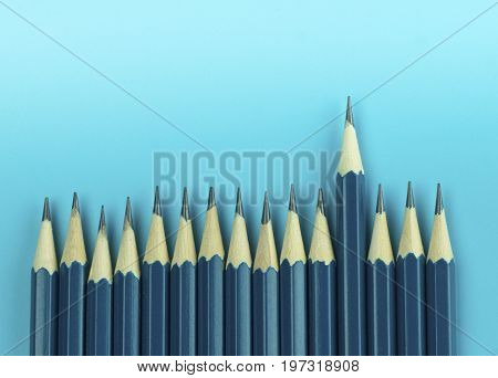 pencils on blue background concept in leader and standout