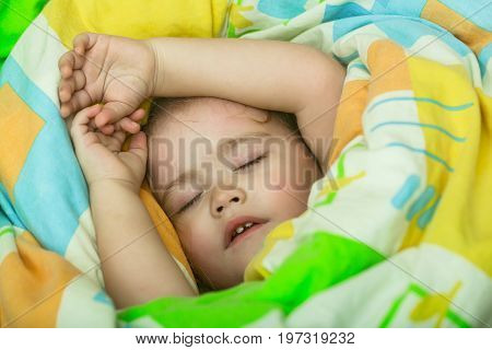 Sleepy baby in colorful blanket. Child sleep in bed. Trust and tenderness. Childhood and happiness. Small baby dreaming.