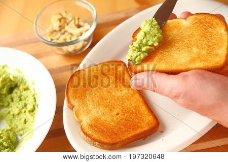 A man spreads mashed avocado on a slice of toast with almond pieces in the background