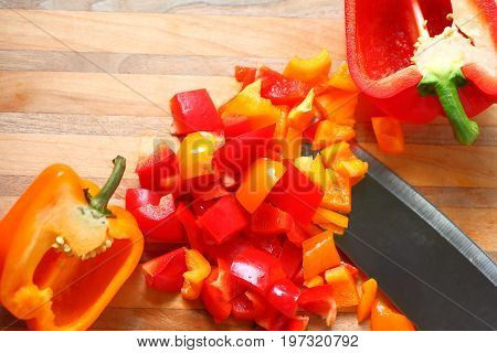 Overhead of red and orange bell peppers chopped and halves with copy space