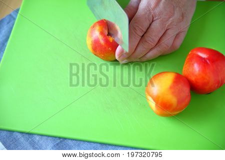 Older man slicing into a fresh nectarine on a green cutting board with room for text