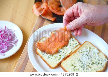 A man puts together a sandwich of smoked salmon and onion on bread with herb mayonnaise