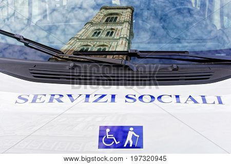 Florence Italy - October 17 2016: Giotto Bell Tower reflected in window of Servizi Sociali Misericordia di Firenze bus Florence Tuscany Italy
