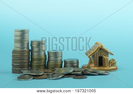pile of coins and home concept in house finance on blue background