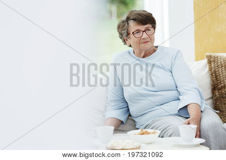 Grandmother in blue outfit is sitting on sofa in common room with yellow wall