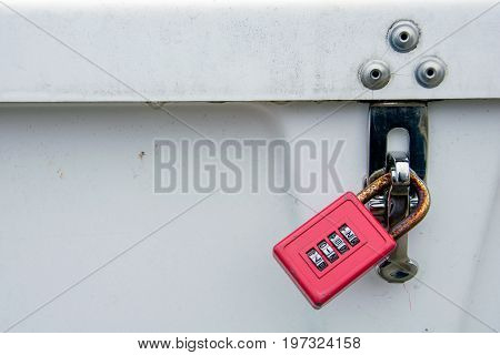 red combination lock on grungy storage box with water droplet