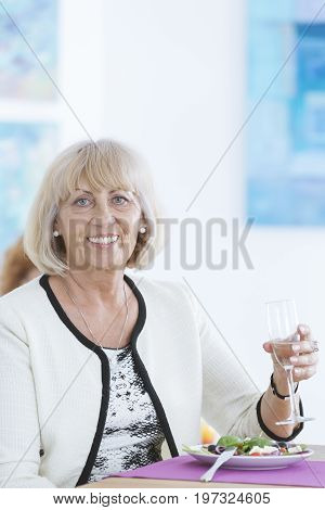 Elder happy lady smiling and holding a glass of champagne