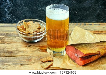 glass of beer smoked salmon on paper a bowl of garlic breadcrumbs on an old wooden table