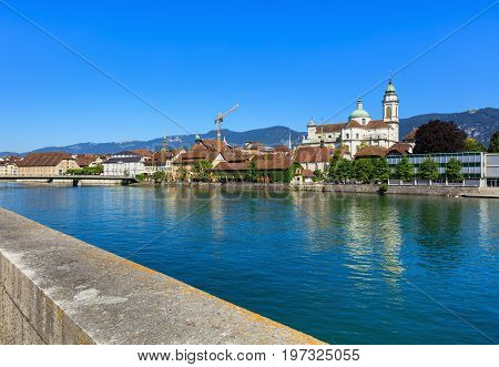 The Aare river in the city of Solothurn, buildings along it, towers of the St. Ursus cathedral and mountains in the background. The city of Solothurn is the capital of the Swiss canton of Solothurn.