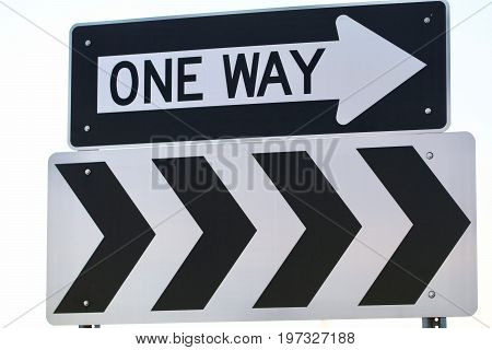 A one way sign made of steel shows.