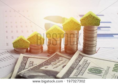 money on stacked of coins to save for house small tree and home on pile with dollar and work finance on wood table with sunlight background concept as investment finance account and stock market