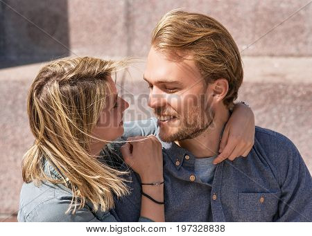 Young caucasian couple embrace and look at each other while dating. Romantic concept
