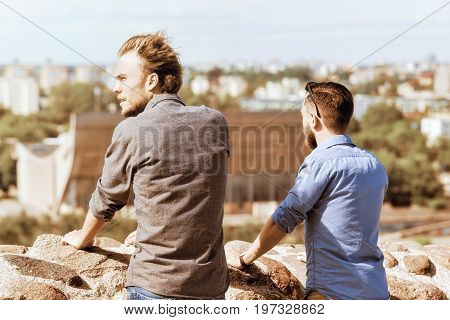 Young Caucasian Buddies Look Into Distance At City Skyline