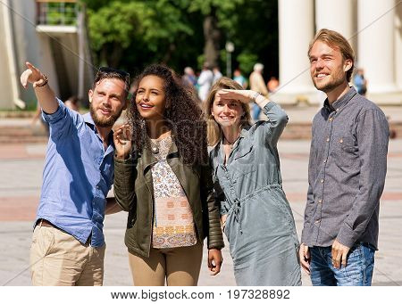 Young Buddy Pointing Direction To Friends In City Street