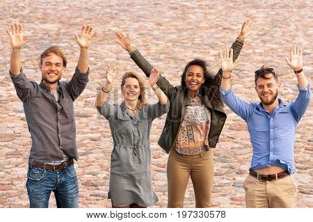 Group Of Young Friends Waving Hands As Greeting Gesture