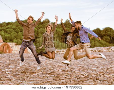 Group Of Smiling Young Multiracial Friends Trying To Jump Up