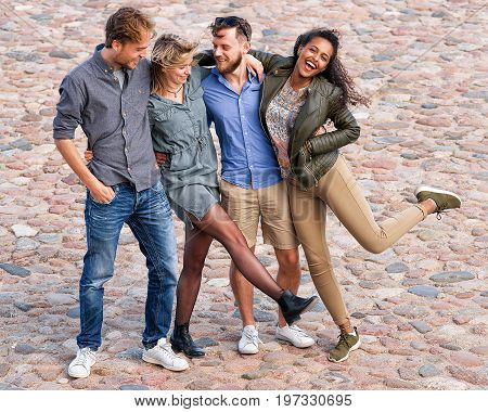 Group Of Smiling Young Friends Raise And Move Their Legs